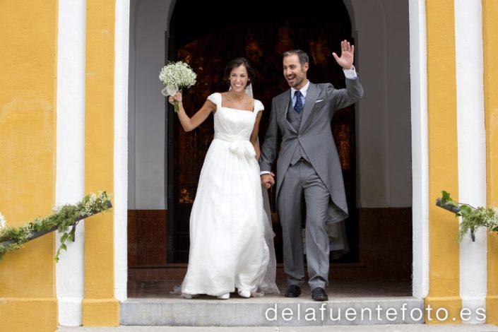 Reportaje de Bodas en Córdoba. Los novios saludan en la salida de la iglesia de Santo Domingo en Córdoba. Reportaje de boda en Córdoba hecho por De la Fuente Fotografía
